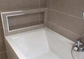 new bathroom with bath and tiles
